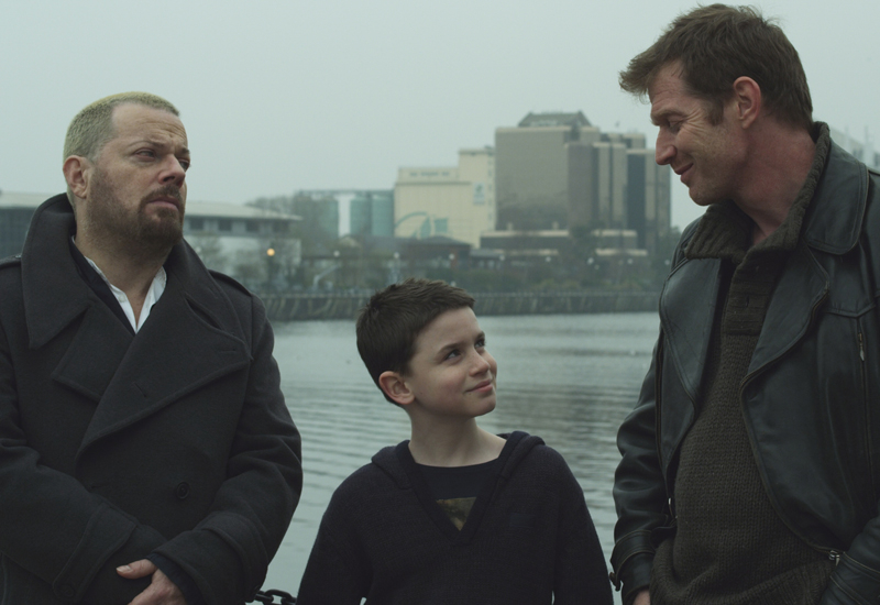 Eddie Izzard, a child and that English bloke out of City of Life pose before Manchester's imposing skyline.