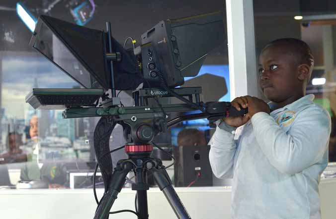A boy learns how to use a studio camera at KidZania London.