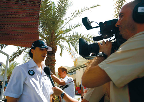 Polish driver Robert Kubica talks with a TV crew. An estimated 750 broadcasting staff covered the Bahrain Grand Prix which attracted a global TV audie