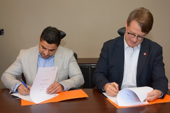 Maaz Sheikh (left) signs the deal.